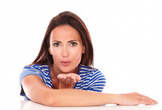 Pretty woman in blue t-shirt blowing a kiss Royalty Free Stock Images