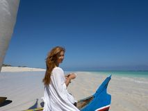 Pretty woman on boat, red hair, drinking tea on the beach royalty free stock image