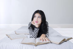 Pretty woman with books on bed Stock Photo