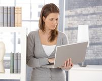 Pretty woman by bookshelf with computer Stock Photo