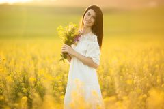 Pretty woman with bouquet of wildflowers in yellow field in sunset lights, summer time. Happy young beautiful woman is wearing white fashion dress with bouquet royalty free stock photo
