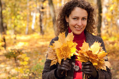 Pretty woman with bouquets of leaves in park Stock Photography