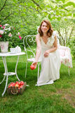 Pretty woman with box of apples havig fun in the summer garden. Outdoor celebration, tea party. Stock Image