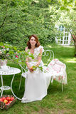 Pretty woman with box of apples havig fun in the summer garden. Outdoor celebration, tea party. Stock Photos