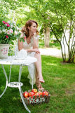 Pretty woman with box of apples havig fun in the summer garden. Outdoor celebration, tea party. Stock Photo