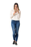Pretty woman in braided shirt smiling while reading cellphone message. Full body length portrait isolated over white background stock image