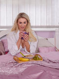 Pretty woman with breakfast in bed Royalty Free Stock Image