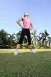 Pretty woman breathing in a park. With outdoor exercise Stock Photo