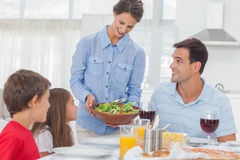 Pretty woman bringing a salad to her family Royalty Free Stock Image