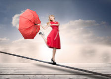 Pretty woman with a broken umbrella over the clouds royalty free stock image
