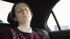 Pretty woman with brown hair in white blouse and maroon sweater is ridinging in traffic in car and just sleeping