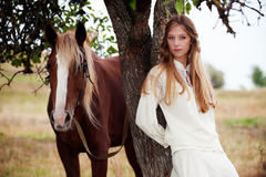 Pretty woman with brown horse Stock Image