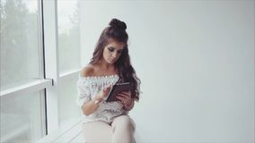 Pretty woman brunette using her tablet on white background near the window stock footage
