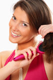 Pretty woman brushing her hair Royalty Free Stock Photography