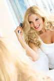 Pretty woman brushing her hair Royalty Free Stock Images