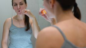 Pretty woman brushing her teeth in a bathroom in the morning. Morning hygiene. stock footage