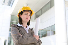 Pretty Woman Business Architect. A young, pretty woman architect inspecting the blueprints Royalty Free Stock Photography