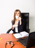 Pretty woman in a business suit sitting at a desk with computer.  woman drinks coffee from a white cup Royalty Free Stock Image