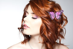 Pretty woman with a butterfly in her red hair - beauty shot Royalty Free Stock Image