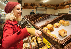 Pretty woman buying scones at bakery Royalty Free Stock Photos
