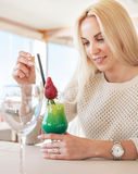 Pretty woman in cafe with bright tropical cocktail. Local focus Royalty Free Stock Photos