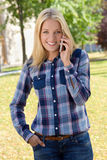 Pretty woman calling by phone in autumn park Royalty Free Stock Photo