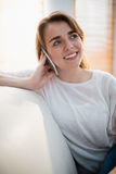 Pretty woman calling on the phone. On the couch in the living room Stock Image