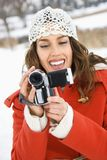 Pretty woman with camera. Smiling Caucasian young adult female in winter clothing pointing video camera at viewer Stock Photo
