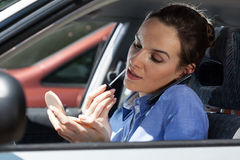 Pretty woman in a car doing makeup while standing in a traffic jam Stock Photo