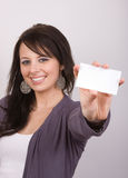 Pretty Woman with Card. A pretty woman holds out a blank white card in one hand. Selective focus on her face Royalty Free Stock Photos