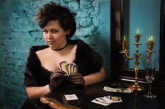 Pretty woman with cards in the vintage interior Stock Image