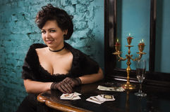 Pretty woman with cards in the vintage interior Royalty Free Stock Photos