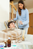 Pretty  woman caring for sick man Royalty Free Stock Photos