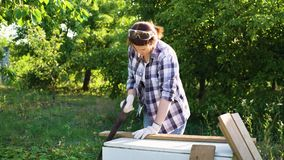 Pretty woman carpenter handsawing wooden plank in sunshine in garden. Adult caucasian female doing carpentry job outside. do it yourself, safety at work, hobby stock video