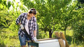 Pretty woman carpenter looks at camera and handsaws plank in sunny orchard. Pretty woman carpenter looks at camera and handsaws wooden plank in sunny orchard stock video