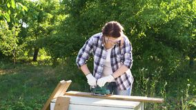 Pretty woman carpenter puts on protective glasses and polishes plank with sander. Pretty woman carpenter puts on protective glasses and polishes wooden plank stock footage