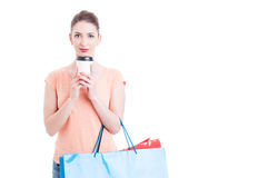 Pretty woman carrying shopping bags and holding coffee paper mug Stock Image