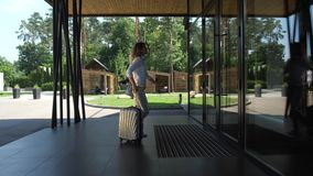 Pretty woman carrying suitcase to hotel entrance. Side view of female in casual clothing carrying suitcase while opening door and entering hotel building stock footage