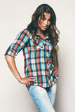 Pretty woman in check shirt and blue jeans. In studio Stock Photos