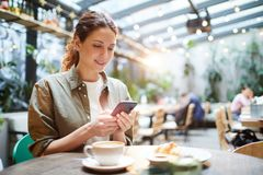 Pretty woman checking messenger in cafe stock images