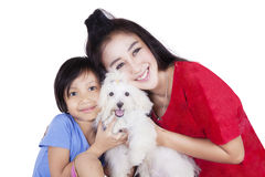 Pretty woman and child embrace dog. Portrait of cheerful young women and little girl embrace a maltese dog together while smiling at the camera Royalty Free Stock Photos