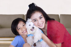 Pretty woman and child holding dog Stock Images