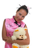 Pretty woman in chinese dress hugging bear Stock Photo