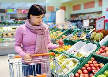 Pretty woman choosing apple at fruit supermarket. Pretty caucasian woman choosing apple during shopping at fruit vegetable supermarket Royalty Free Stock Images