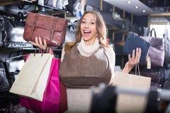 Pretty woman choosing bag among assortment Royalty Free Stock Photography