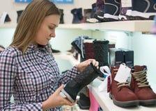 Pretty woman choosing winter boots. Pretty woman choosing children`s winter boots in the mall Royalty Free Stock Photo