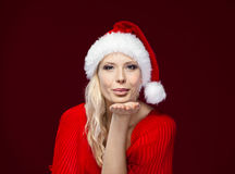 Pretty woman in Christmas cap blows kiss Royalty Free Stock Photography