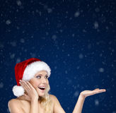 Pretty woman in Christmas cap gestures palm up Stock Photos