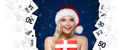 Pretty woman in Christmas cap hands item of the day Royalty Free Stock Photography