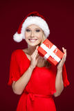 Pretty woman in Christmas cap hands a present Royalty Free Stock Photo